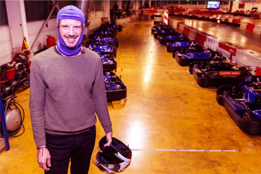 Foto eines Mannes, der vor geparktem Kart steht